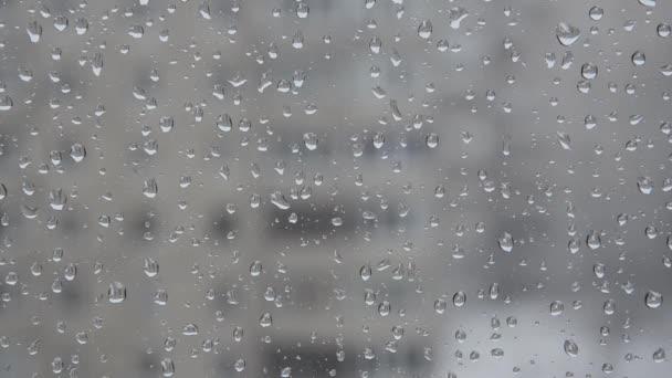 Dešťové kapky na okno na pozadí města během zimního dne. Zavřít kapky na sklo na pozadí rozmazaných domů. Kapky vody na sklo s rozmazanými budovami.