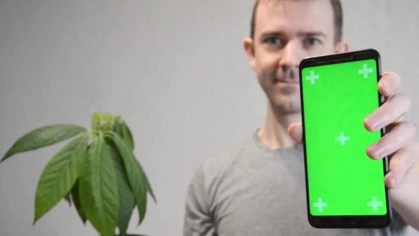 Detailní záběr telefonu se zelenou zástěnou z chromakey makey makety se stopařskými značkami v ruce bělocha. Zelená obrazovka a chroma klíč. Koncept doporučení.