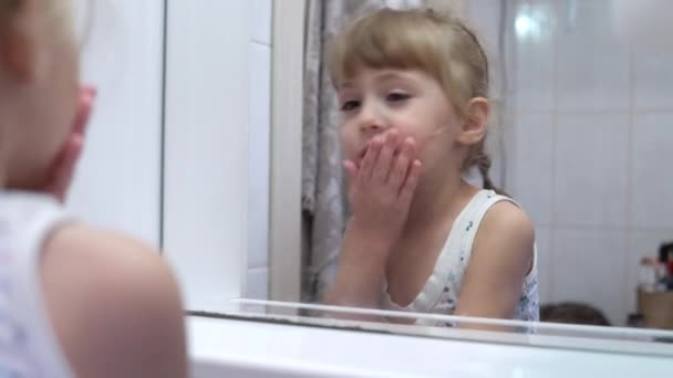 Girl washing her face in front of the mirror in the bathroom