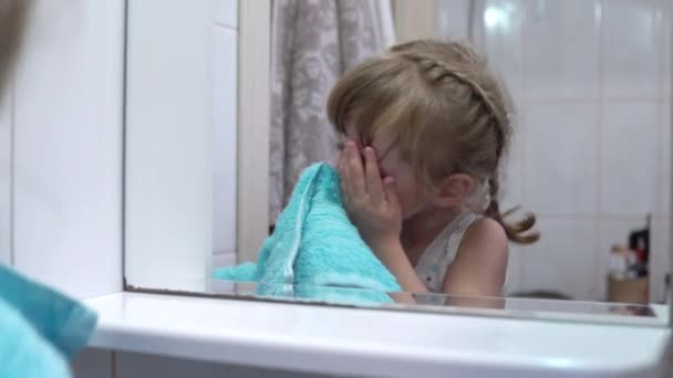 Girl wipes her face with a towel in front of the mirror