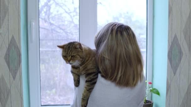 Žena v županu s kočkou v náručí stojí před oknem a hladí kočku.