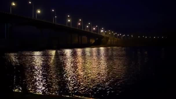 Russian city road bridge across the river. The night bridge glows with lanterns and reflects glare on the water