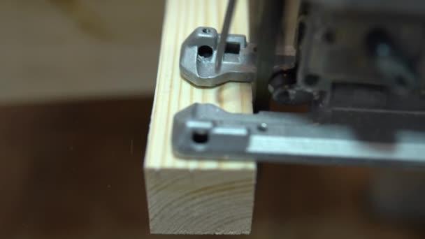 Detailní záběr řezání kusu dřeva pilou. Opravte se doma