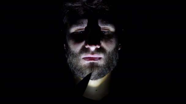 Features of a male, bearded face, backlit in the dark. Close-up of a mans face in the dark who holds a knife in his hand