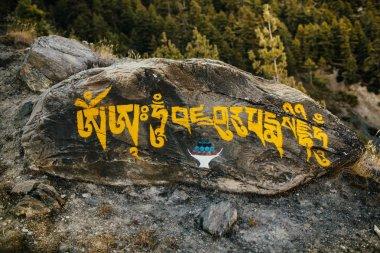 Mantra stone on the path in Himalayas. Trekking around Annapurna.