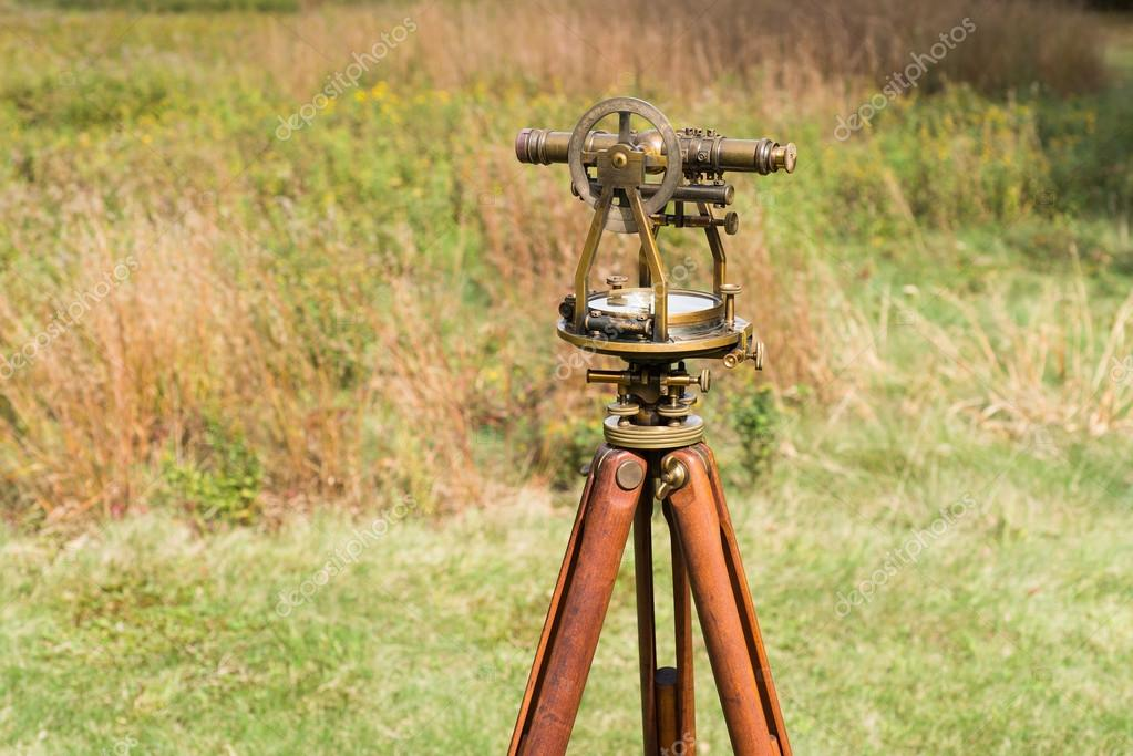 Close up of Vintage Surveyor's Level (Transit, Theodolite) with wooden Tripod in a field.