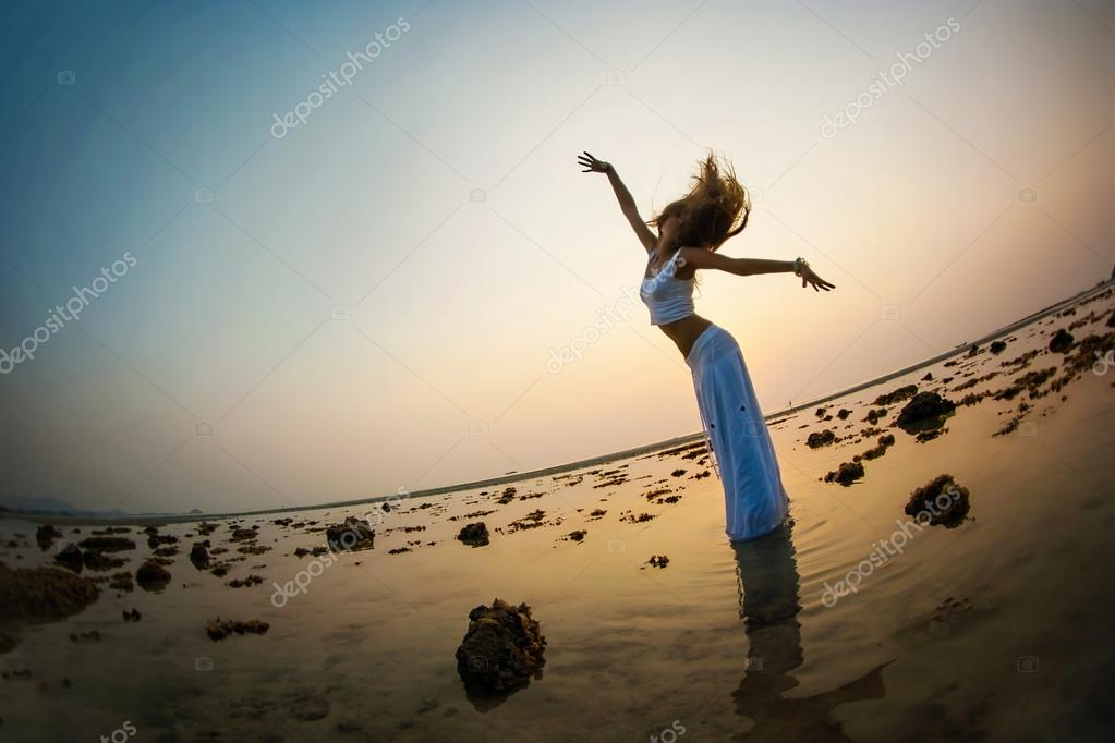 woman is dancing on the beach at sunset