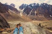 Legs of traveler sitting on a high mountain
