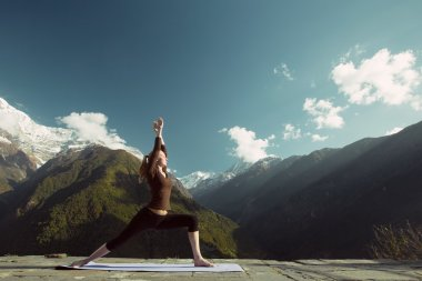 Woman in mountains doing yoga exercises