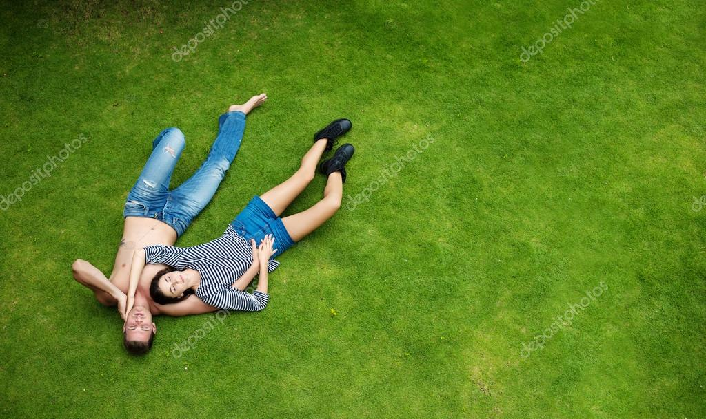 Happy Love Young couple lying on green grass