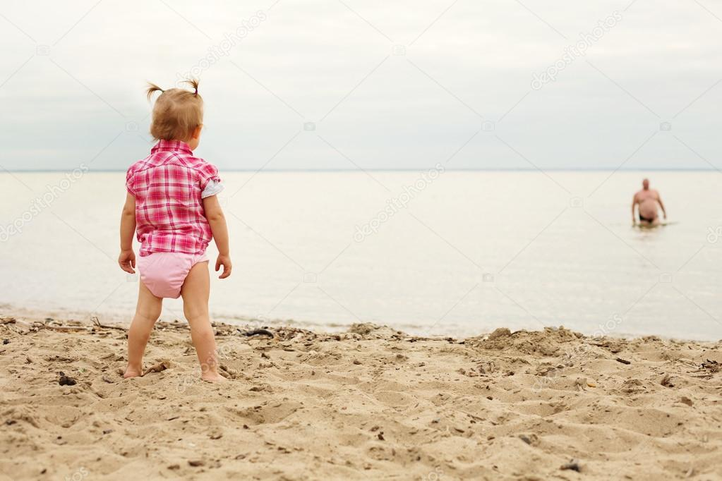 Little girl standing on the beach