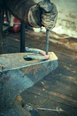 Blacksmith forges a horseshoe