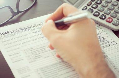 Man filling individual income tax return form