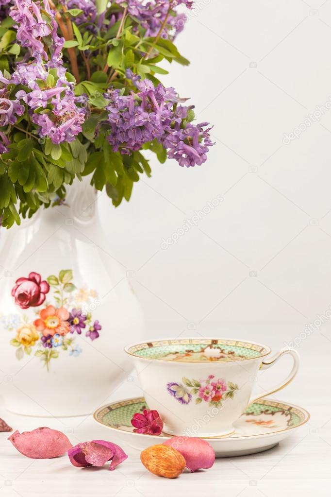 Tea with  lemon and bouquet of  lilac primroses on the table