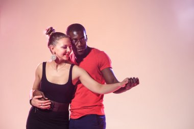 Young couple dances social Caribbean Salsa, studio shot