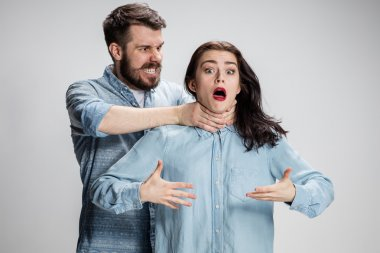 The quarrel men and women. Man strangling a woman on gray background