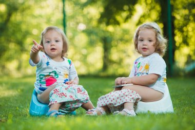 The two little baby girls sitting on pottys against green grass