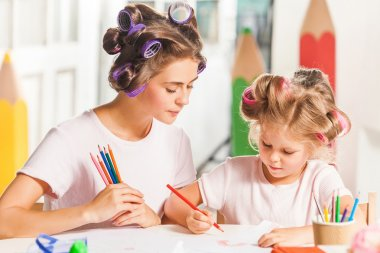 The young mother and her daughter drawing with pencils at home stock vector