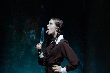 Portrait of a young girl in school uniform as killer woman
