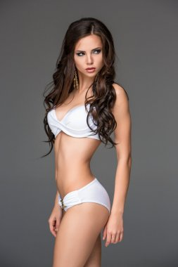 Sexy young brunette woman with her hair posing in a white bikini . Studio, on gray background