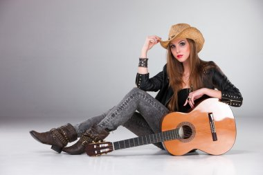 The beautiful girl in a cowboys hat and acoustic guitar.