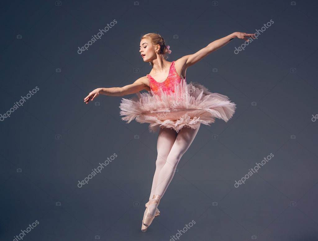 Hermosa bailarina femenina sobre un fondo gris. Bailarina es
