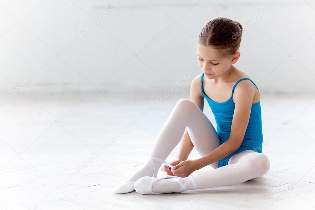 Beautiful little ballerina in blue dress for dancing puting on foot pointe shoes