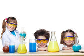 Photo The three cute children at chemistry lesson making experiments on white background