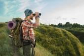 Fotografia Giovane uomo caucasico con la condizione di zaino sulla cima di collina