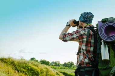 Young smilimg caucasian tourist with backpack  standing on the top of hill against blue sky background and looking through binoculars stock vector