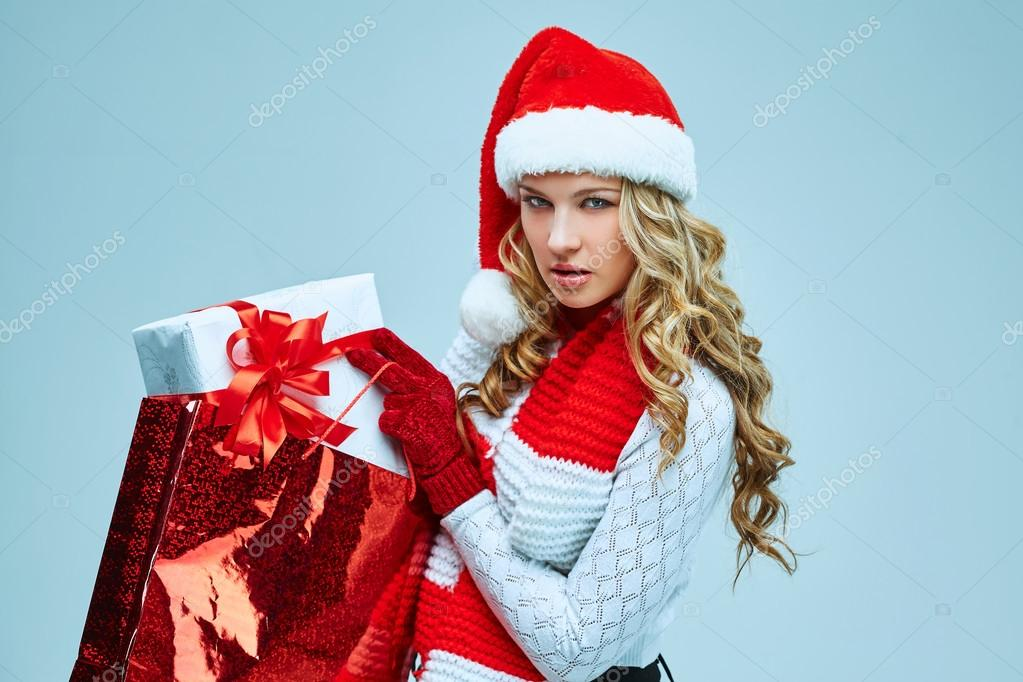 316d464d3cf2 Beautiful young woman in Santa Claus clothes with a gift on a gray  background — Photo by vova130555@gmail.com| ...