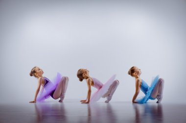Three little ballet girls sitting in tutus and posing together