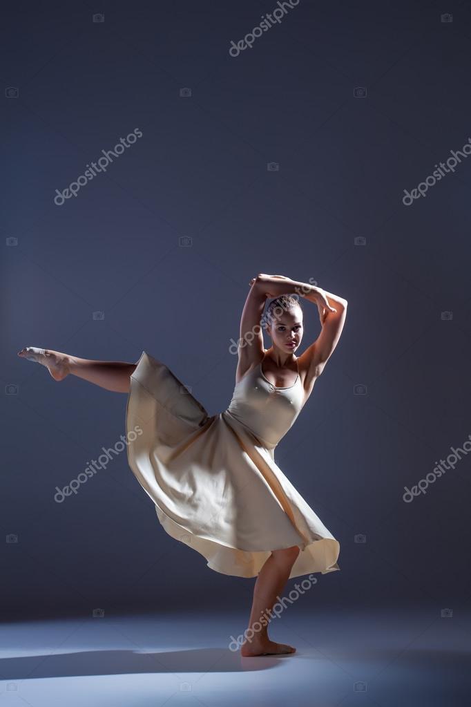 c886032ab5bf Unga vackra dansare i beige klänning dans på grå bakgrund — Stockfoto