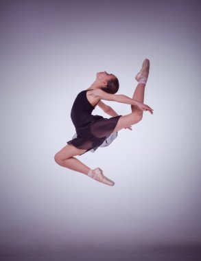 The silhouette of young ballet dancer jumping on a lilac  background.