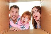 rodina v kartonové krabici, která je připravena pro stěhování