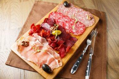 Variety of meats, sausages, salami, ham, olives