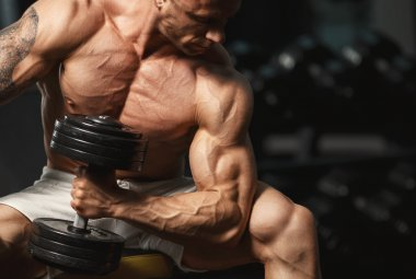 strong bodybuilder doing exercise with dumbbell