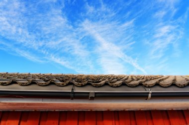 Roof with gray tiles on background of blue sky