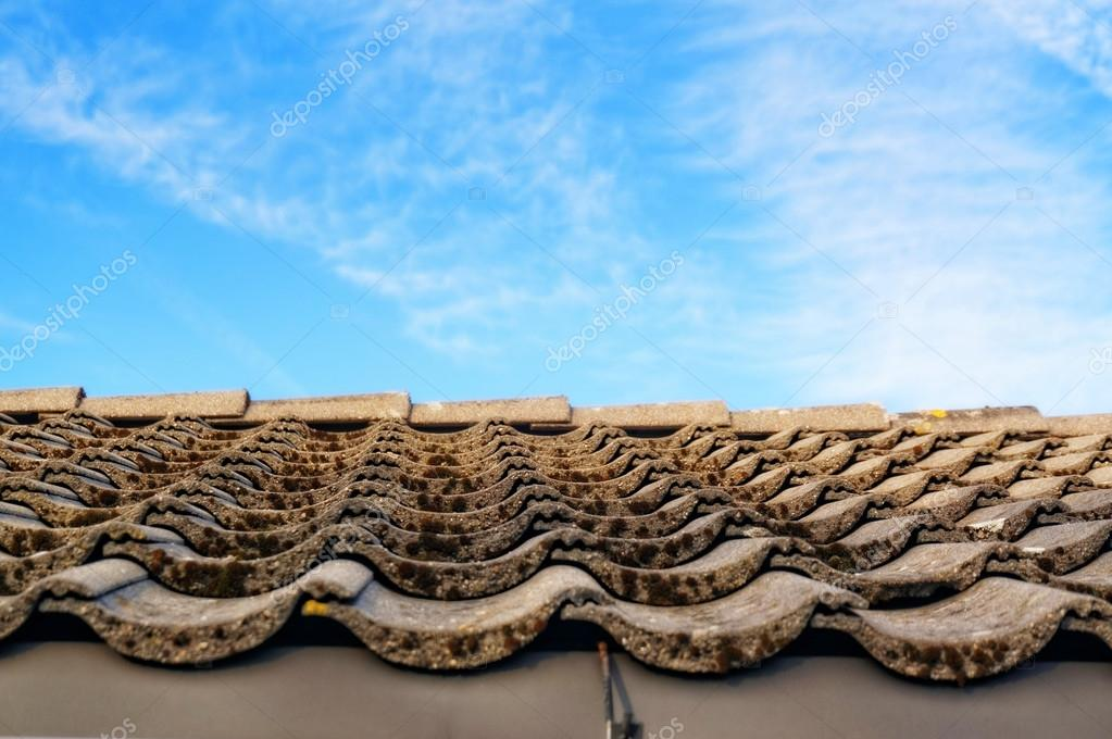 Roof with gray tiles on the tabs on background of blue sky