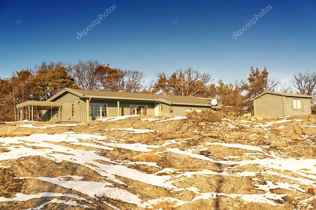 Gray cottage on a high rocky coast, around rocks