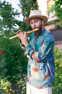 Hippie man playing a woody flute