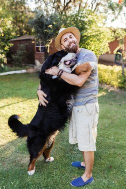 Man hugging a big black dog