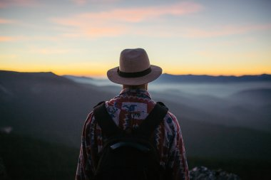 Man in hat with bag looking at the sunset