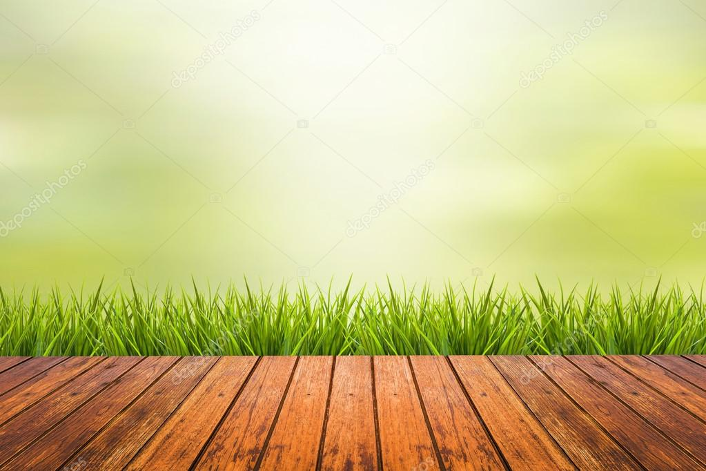 grass with green blurred background and wood floor