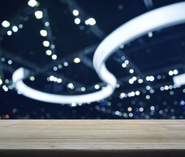 Empty wooden table over defocused light and shadow of shopping m