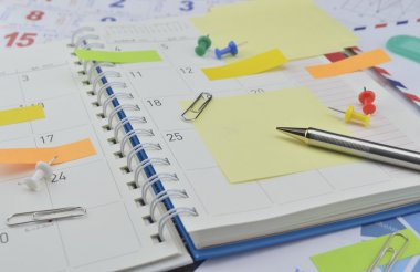 Pen with post It notes and pin on business diary page