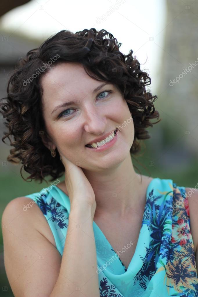 Retrato De Una Sonriente Mujer Joven Con El Pelo Corto Rizado Oscuro - Pelo-corto-rizado-mujer