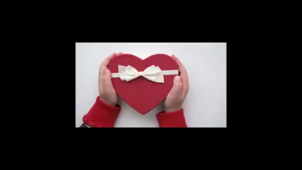 Girl hands hold red heart gift box with white ribbon. Valentine day