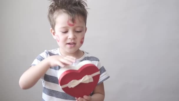 Happy little boy holding heart gift box on valentine day. Close up.