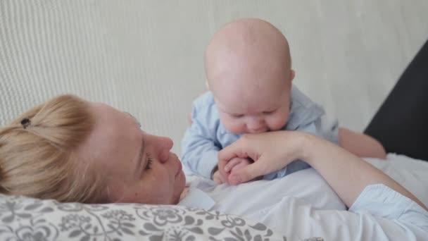 4k. glückliche Mütter mit kleinem Baby auf dem Bauch.